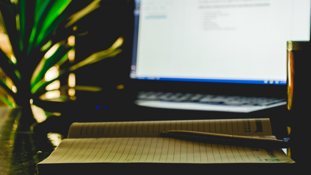 A pen,a diary,a coffee mug and a laptop in the frame.